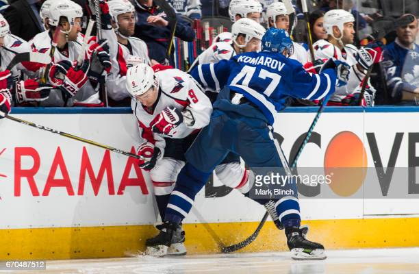 Dmitry Orlov of the Washington Capitals is checked by Leo Komarov of the Toronto Maple Leafs during the third period in Game Three of the Eastern...
