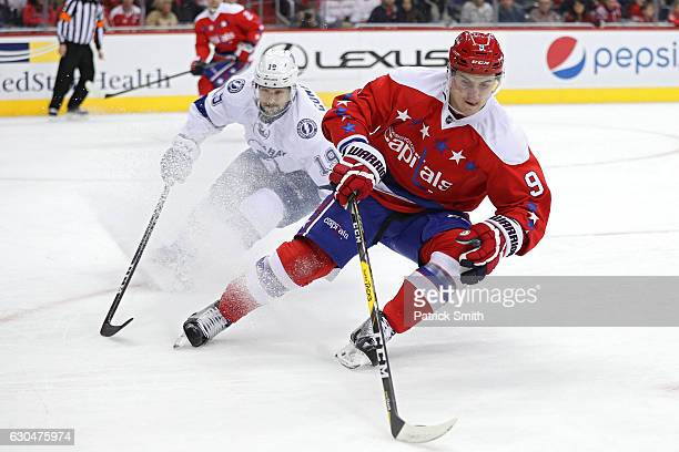 Dmitry Orlov of the Washington Capitals skates past Cory Conacher of the Tampa Bay Lightning during the first period at Verizon Center on December 23...