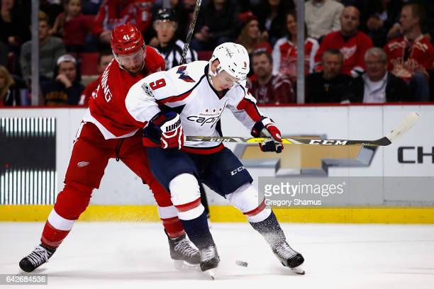 Dmitry Orlov of the Washington Capitals tries to control the puck in front of Luke Glendening of the Detroit Red Wings during the second period at...