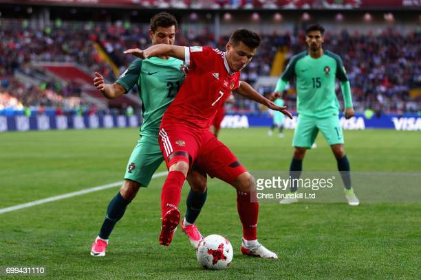 Dmitry Poloz of Russia tangles with Cedric of Portugal during the FIFA Confederations Cup Russia 2017 Group A match between Russia and Portugal at...