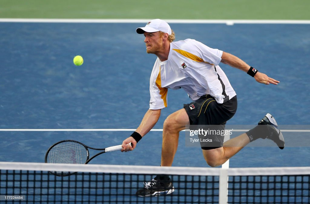 Dmitry Tursunov of Russia returns a shot to Jurgen Melzer of Austria in the quarterfinals match during day 5 of the Winston-Salem Open at Wake Forest University on August 22, 2013 in Winston Salem, North Carolina.