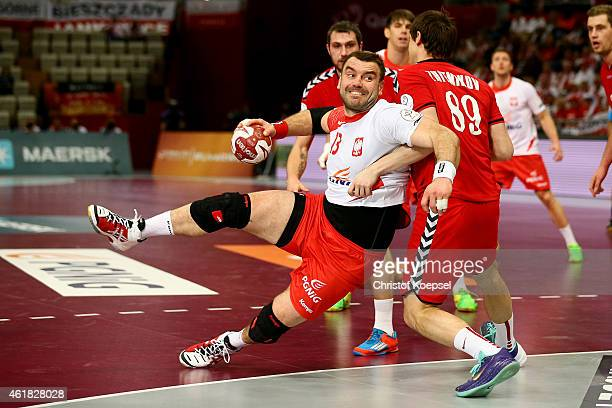 Dmitry Zhitnikov of Russia defends against Bartosz Jurecki of Poland during the IHF Men's Handball World Championship group D match between Poland...