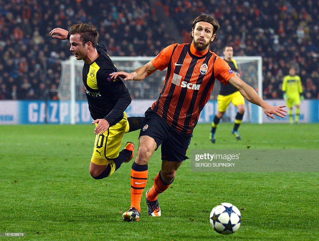 Dmytro Chygrynskiy (R) of FC Shakhtar fights for a ball with Mario Goetze (L) of Borussia Dortmund during their UEFA Champions League round 16 football match in Donetsk on February 13, 2013.