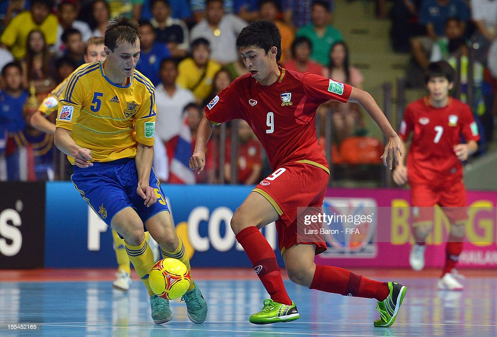 Dmytro Sorokyn of Ukraine challenges Suphawut Thuenklang of Thailand during the FIFA Futsal World Cup Group A match between Thailand and Ukraine at Indoor Stadium Huamark on November 4, 2012 in Bangkok, Thailand.