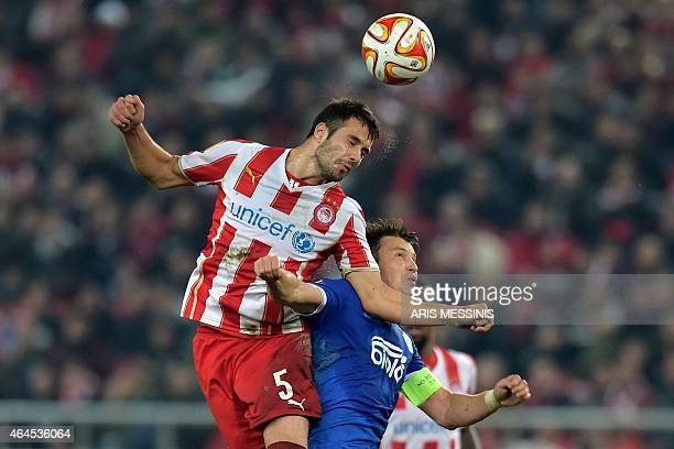 FC Dnipro' Ukrainian midfielder Ruslan Rotan and Olympiacos' Serbian midfielder Luka Milivojevic go for a header during the UEFA Europa League Round...