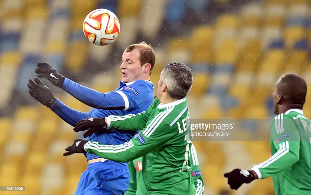 FC Dnipro's Roman Zozulya (L) and AS Saint-Etienne's Fabien Lemoine (C) vie for the ball during the UEFA Europa League Group F football match FC Dnipro vs AS Saint-Etienne in Kiev on December 11, 2014. AFP PHOTO/ SERGEI SUPINSKY