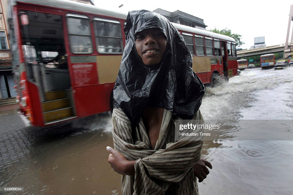Dnyaneshwar Kasbe, a street boy, who earns his daily wages by cleaning cars on the signal at Dadar TT has no work due to heavy rain on July 31, 2005 in Mumbai, India. He bought this plastic bag for Re.1 and used it as a raincover.