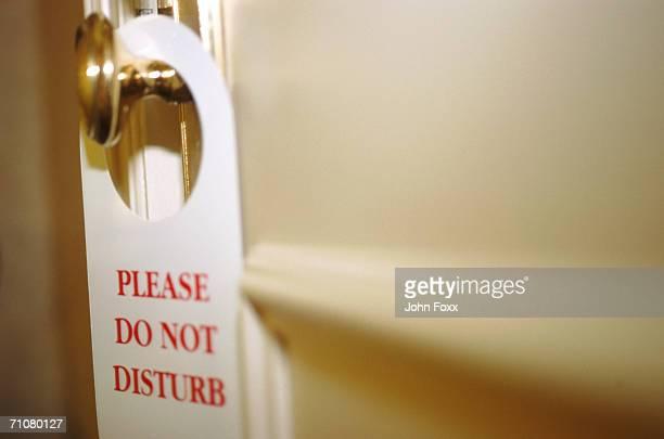 Do not disturb sign hanging from hotel door handle