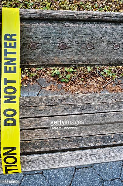 'Do Not Enter' tape attached to city park bench