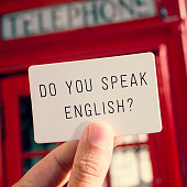 a man holding a signboard with the text do you speak english? with a typical british red telephone booth in the background