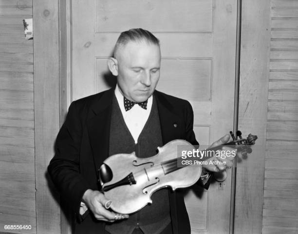 P 'Doc' Davis director and performer with The Bog Trotters mountain music band is photographed with a handmade violin for the CBS Radio program...