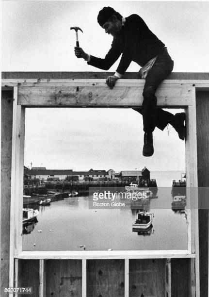 Doc Legg of Gloucester has a picture preview view of Motif as he rebuilds a candy store on Rockport Harbor in Rockport Mass on Dec 31 1982