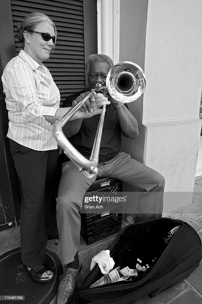'Doc' Lewis, a street musician in the French Quarter, plies his trade on a street corner near Chartes St. in New Orleans. Playing 'all the instruments' for 46 years, he has tourists lay their hands on his trombone and partake in one of thousands of songs he knows. The French Quarter, relatively unscathed after Katrina, struggles with a lack of business stemming from reduced tourism and local population. For this photographer, the number of street musicians was greatly reduced from the time right before Katrina, the time of my last visit.