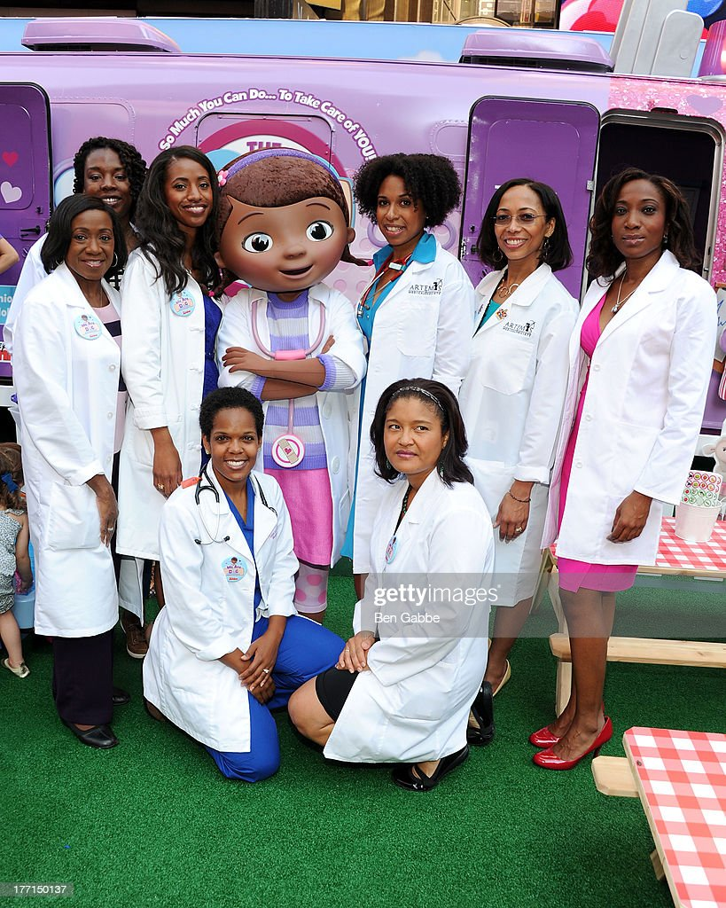 Doc McStuffins (C) poses with doctors at the Doc Mobile Tour at the Disney Store on August 21, 2013 in New York City.