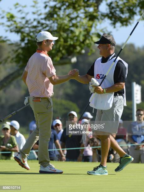 Doc Redman celebrates with his caddie Dean Emerson on the 18th hole after making a birdie during the second round of the USGA US Amateur Championship...