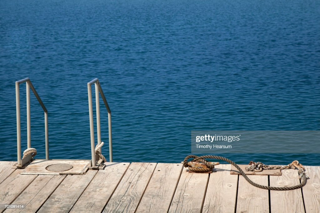 Dock with ladder into the ocean and rope for boat tie-up : Stock Photo