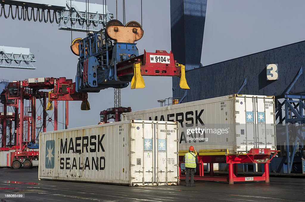 A dock worker directs a gantry crane as it collects a shipping container during loading operations for the Maersk Mc-Kinney Moeller Triple-E Class container ship, operated by A.P. Moeller-Maersk A/S, in the Port of Bremerhaven in Bremerhaven, Germany, on Monday, Nov. 11, 2013. A.P. Moeller-Maersk A/S's container-shipping line, the world's largest, reported an 11 percent increase in third-quarter profit after cost cuts countered a decline in freight rates. Photographer: Kristian Helgesen/Bloomberg via Getty Images
