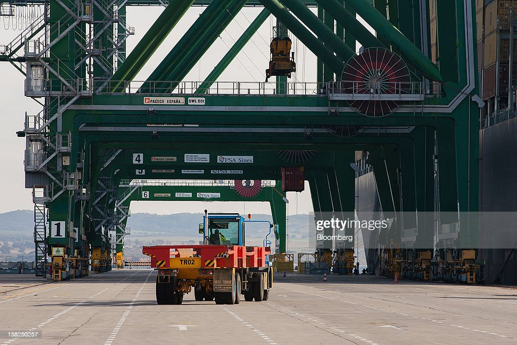 A dock worker drives a truck towards gantry cranes unloading shipping containers from the cargo vessel MSC Renee at the open deep-water Port of Sines in Sines, Portugal, on Tuesday, Dec. 11, 2012. The Portuguese government is ready to implement additional measures in 2013 if there are slippages in meeting budget targets, the European Commission said. Photographer: Mario Proenca/Bloomberg via Getty Images