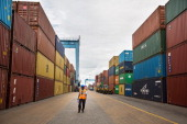 A dock worker for the Kenya Ports Authority a staterun company walks between stacked shipping containers at Mombasa port in Mombasa Kenya on Friday...