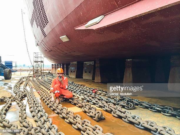 Dock worker in a shipyard talking on a walkie talkie