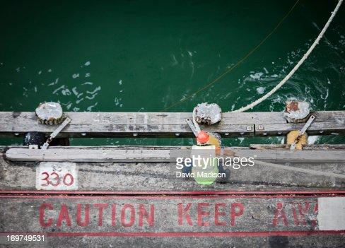 Dock worker tying hawser rope to pier bollard. : Stockfoto