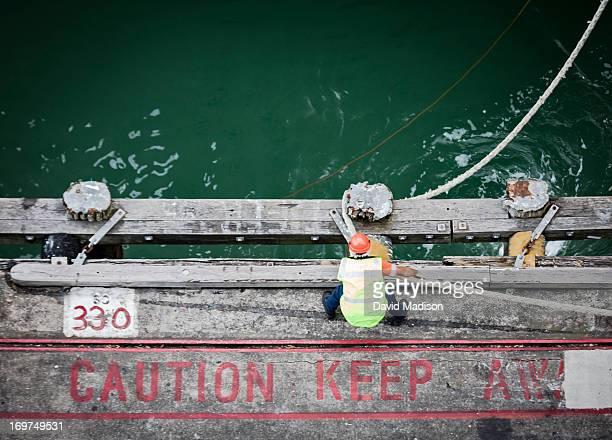 Dock worker tying hawser rope to pier bollard.