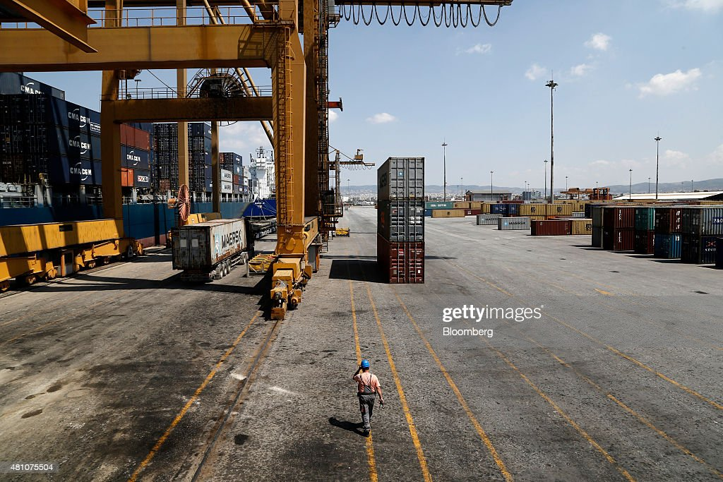 A dock worker walks on the dockside as a gantry crane loads shipping containers at Thessaloniki port operated by Thessaloniki Port Authority SA in...