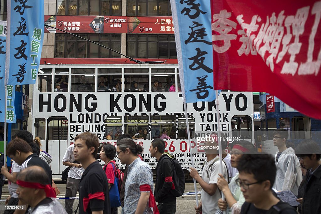 Dock workers carry flags and chant slogans during a Labor Day march in Hong Kong, China, on Wednesday, May 1, 2013. Thousands of Hong Kong residents took to the streets today for Labor Day marches to petition for better labor conditions and in support of strike action by workers at docks operated by billionaire Li Ka-shing. Photographer: Jerome Favre/Bloomberg via Getty Images