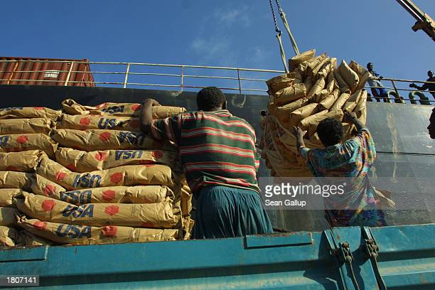 Dock workers load USdonated bags of wheat destined for Ethiopia onto trucks February 21 2003 in Djibouti Town Djibouti The Food and Agricultural...