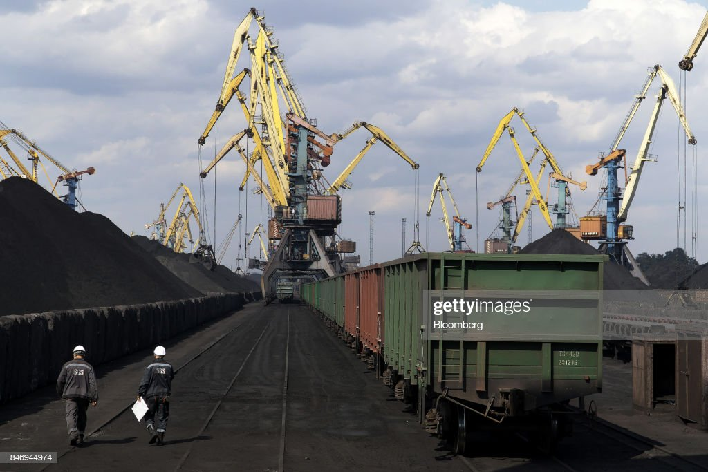 Dock workers pass freight wagons waiting to transport the first shipment of anthracite coal from U.S. supplier XCoal Energy & Resources LLC, for state energy firm Centrenergo PJSC, at Yuzhny Port, near Odessa, Ukraine, on Wednesday, Sept. 13, 2017. A Pennsylvania company will send 700,000 tons of coal to Ukraine in a deal the administration of President Donald Trump heralded as an important tool to undercut the power Russia has over its European neighbors. Photographer: Vincent Mundy/Bloomberg via Getty Images