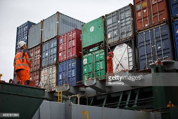 Dock workers secure shipping containers on the deck of the cargo ship Herm operated by Unitas GmbH at Europe Container Terminals BV Delta Terminal in...