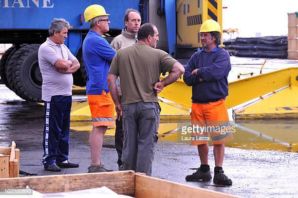 Dock workers stand near the place where a truck driver was killed at the industrial port of Livorno on June 17 2010 in Livorno Italy So far two...