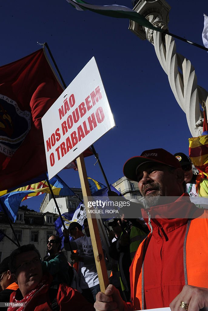 A docker holds a placard reading 'Don't steal our jobs' at the Municipio Square in Lisbon before a demonstration on November 29, 2012. Dockers of Lisbon harbour have been on strike for two months in protest against the reform of their working arrangements currently under discussion y the government.