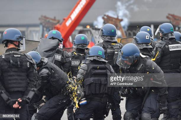 Dockers demonstrating against the labour law reform and the ecologic transition throw eggs at French gendarmes on the sidelines of the inauguration...