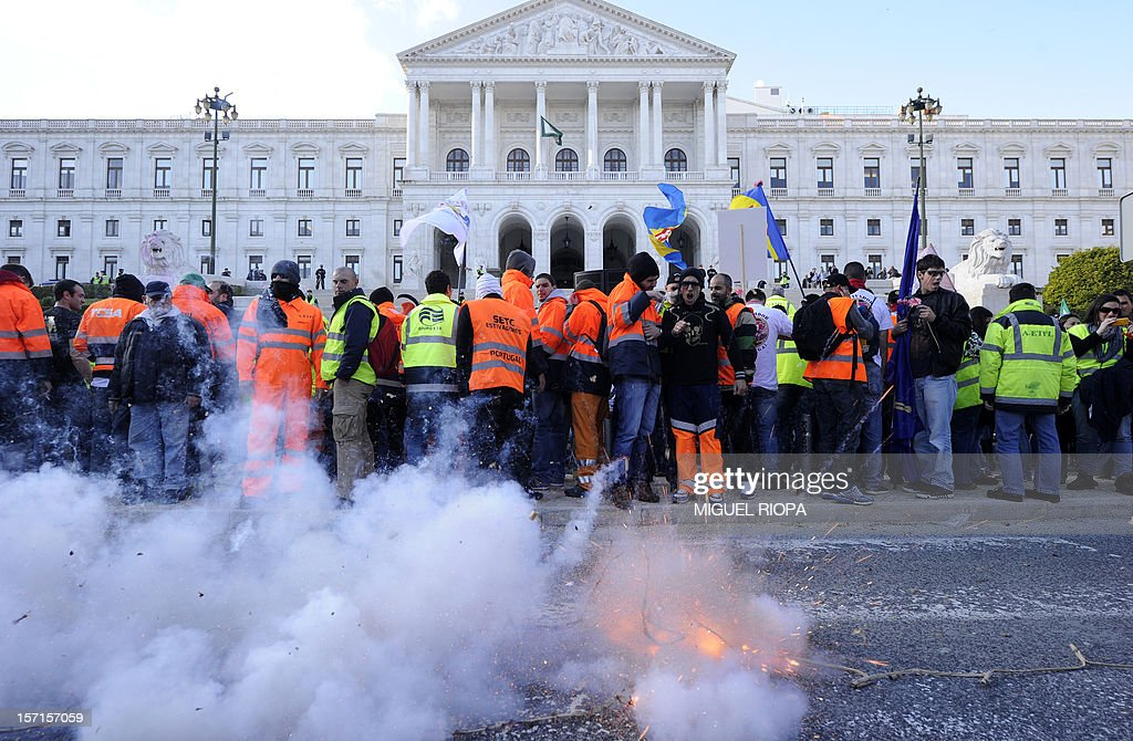 Dockers light firecrackers during a demonstration in front of the Portuguese Parliament on November 29, 2012 in Lisbon. Dockers of Lisbon harbour have been on strike for two months in protest against the reform of their working arrangements currently under discussion by the government.