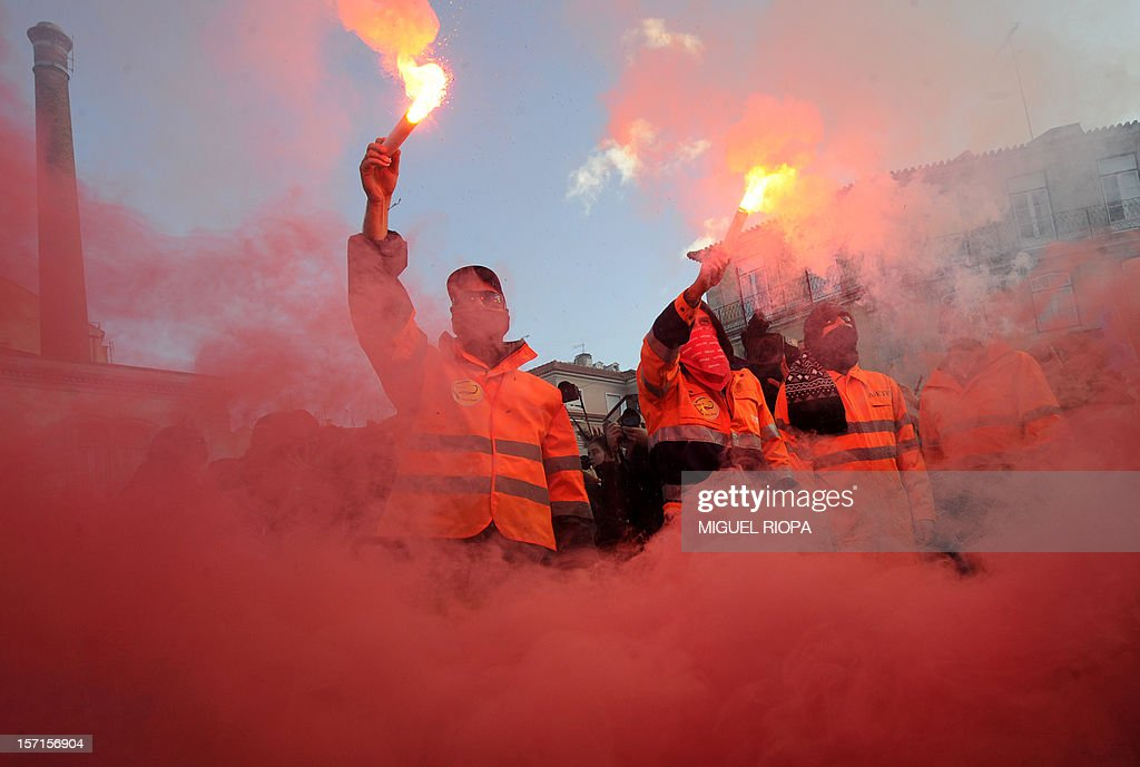 Dockers light flares during a demonstration next to the Portuguese Parliament on November 29, 2012 in Lisbon. Dockers of Lisbon harbour have been on strike for two months in protest against the reform of their working arrangements currently under discussion by the government.