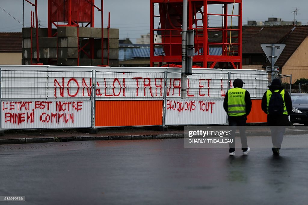 Dockers walk past slogans sprayed onto a fence, near a blockade onto a main road leading to downtown Rouen, northwestern France, on May 31, 2016 to protest against the government's planned labour law reforms. Insriptions read (From L) 'The State is our common ennemy', 'No to the Labour Law' and 'Let's block everything'. / AFP / CHARLY