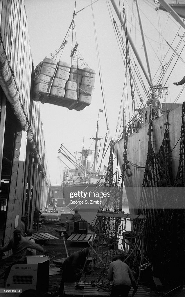 Dockhands use a crane to load a ship at the Norfolk & Western Railway dock, Norfolk, Virginia, December 1961.