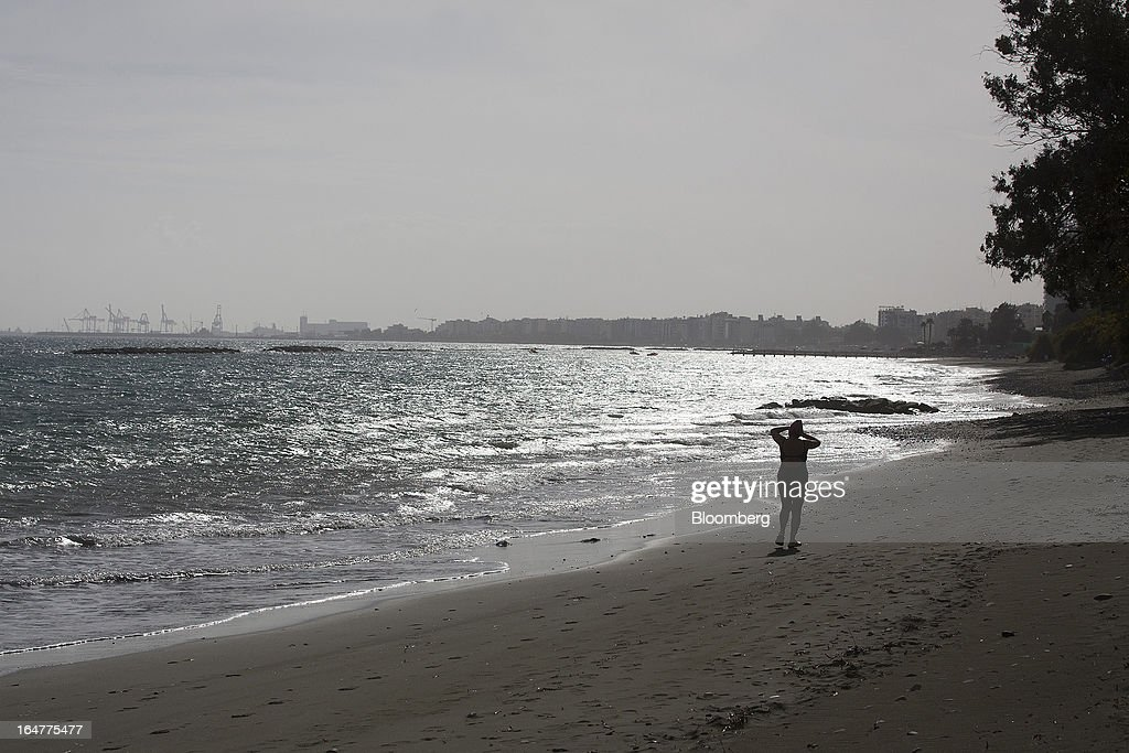 Dockside cranes stand in the distance as a woman walks along the beach in Limassol, Cyprus, on Wednesday, March 27, 2013. The ECB said on March 25 it won't stop the Cypriot central bank from providing the island's banking sector with emergency funding. Photographer: Simon Dawson/Bloomberg via Getty Images