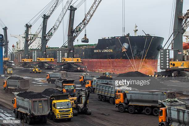 Dockside cranes unload coal from the Genco Shipping and Trading Ltd Genco London ship as tipper trucks transport coal at the Kirshnapatnam Co port in...