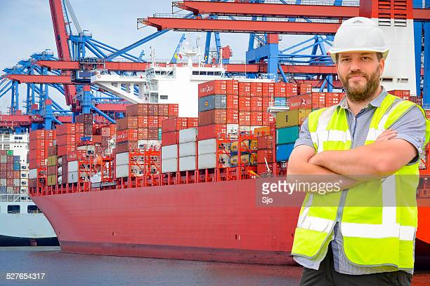 Dockworker in port in front of container ships.