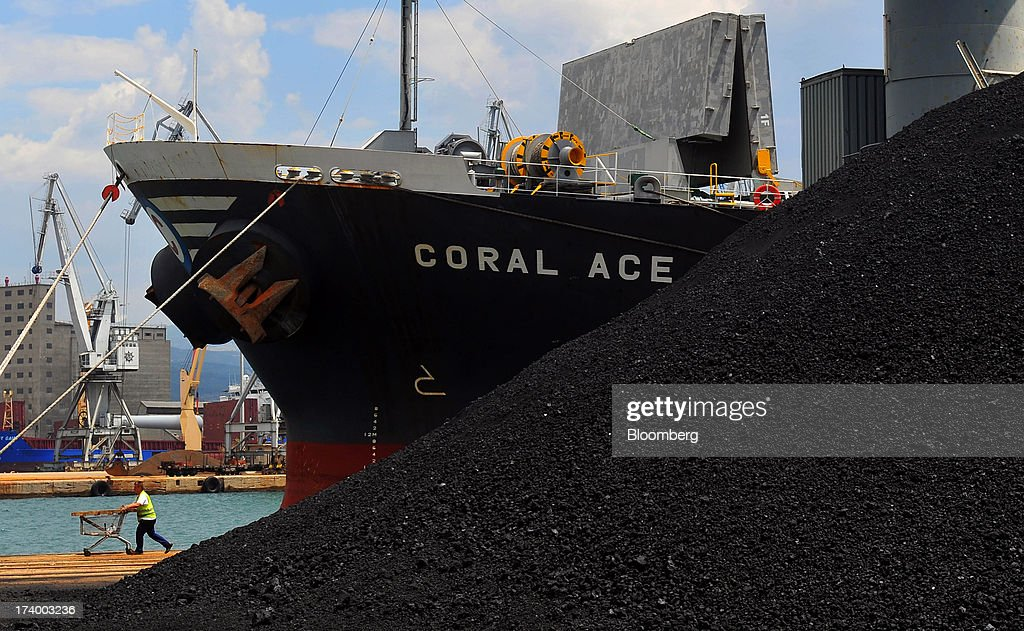 A dockworker pushes a shopping cart past coal supplies off loaded from the cargo ship 'Coral Ace' at Thessaloniki Port, operated by Thessaloniki Port Authority SA, in Thessaloniki, Greece, on Thursday, July 18, 2013. Russian Railways is interested in buying Thessaloniki Port and Greek rail operator Trainose SA as one single unit, newspaper Real News reported, citing an interview with the Russian company's CEO Vladimir Yakunin. Photographer: Oliver Bunic/Bloomberg via Getty Images