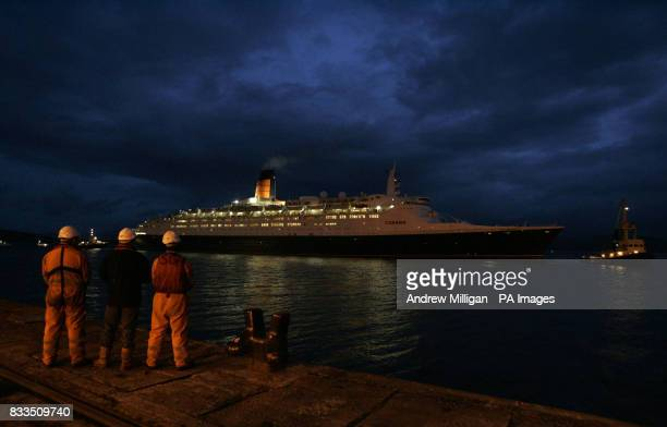 Dockworkers await the arrival of the QE2 at the Ocean Terminal on the Firth of Clyde early this morning
