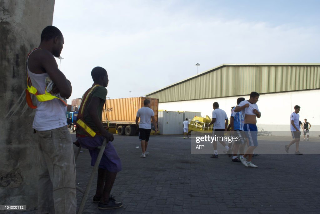 Dockworkers watch sailors from the Argentinian frigate Libertad seized in a port in Ghana in connection with a debt dispute, play football on October 11, 2012 at Tema Port near Accra. A judge in Ghana on October 11, 2012 rejected a bid by Argentina to have one of its warships released from a port near Accra, where it is being held under a court order linked to a debt dispute.