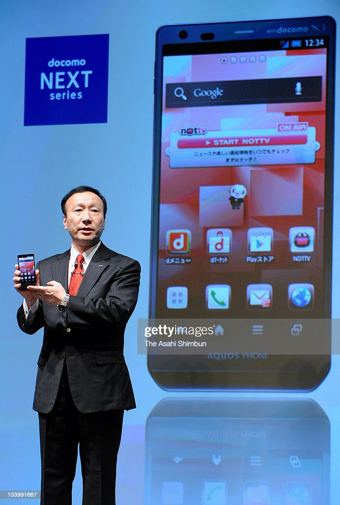 NTT DoCoMo Co President Kaoru Kato displays its new mobile phones during their unveiling session on October 11, 2012 in Tokyo, Japan. The biggest mobile phone company also announced to launch social games.
