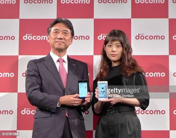 NTT DoCoMo President Kazuhiro Yoshizawa and actress Mitsuki Takahata pose with new mobile phones of NTT DoCoMo during the unveiling on October 19...