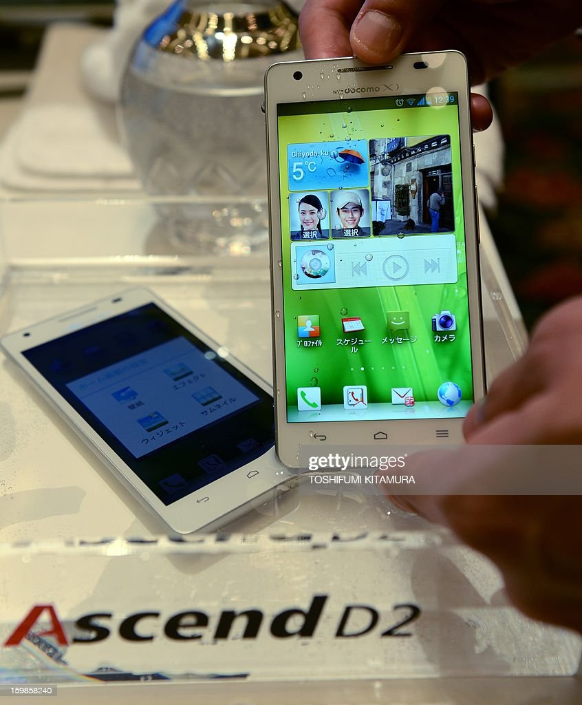 Docomo worker demonstrates the company's new water-proof smartphone, Ascend D2 HW-03E, during the 2013 Spring lineup press preview in Tokyo on January 22, 2013. The new lineup of 11 smartphones and tablets plus one mobile Wi-Fi router will launch in sequence beginning on January 25 in Japan.