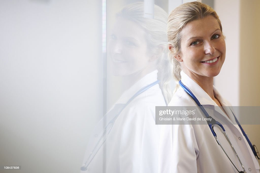 Doctor against a window, smiling : Stock Photo