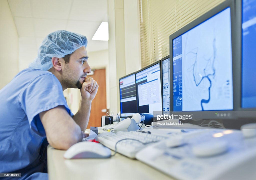 Doctor analyses scan of aneurism : Stock Photo