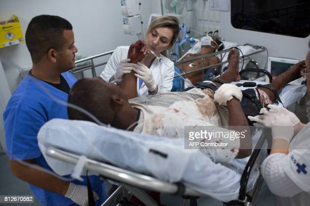 A doctor and a nurse assist a patient who was beaten and shot in the hand at the emergency room of the Cidade de Deus shantytown Emergency Care...